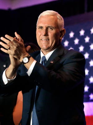 Republican vice presidential candidate, Indiana Gov. Mike Pence applauds as he arrives at a campaign stop in Rochester, N.H., Sunday.