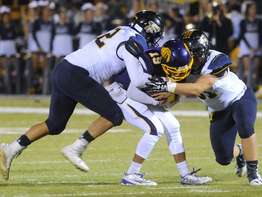 A pair of Stephenville defenders combine to tackle Wylie's Zach Smith (19) during a game on Nov. 4, 2016 at Bulldog Stadium.