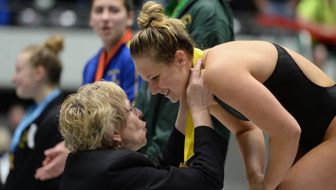 Richmond High School principal and member of the IHSAA board Rae Woolpy talks to Centerville High School's Brooke Madden after presenting her with a fourth place ribbon during the IHSAA diving state finals Saturday, Feb. 13, 2016 at the IU Natatorium on the campus of IUPUI in Indianapolis.