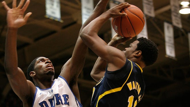 Duke forward Amil Jefferson (21) defends against Michigan guard Nik Stauskas (11) on Tuesday at Cameron Indoor Stadium.