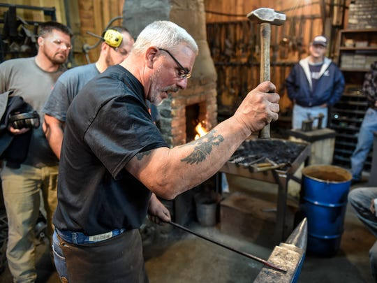 Ken Zitur works with a hammer and hot iron while demonstrating techniques during a Blacksmithing for Veterans event Friday, Nov. 10 at Ken's Custom Iron near Avon.