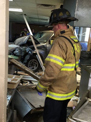 A Jackson firefighter surveys the scene of a fatal vehicle crash in the kitchen of Gateway Rescue Mission.