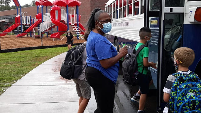 APA bus driver Edna Sheffield helps students with hand sanitizer as they board the bus.