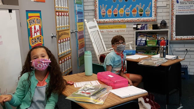 Parrott 3rd graders Lola Thompson and Declan Farrar, both of New Bern, enjoy being back in the classroom.