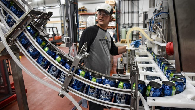 Matt Studer watches as empty cans are prepared for filling Wednesday, May 24 on the first day of production at the new Beaver Island Brewing Company facility in St. Cloud. Six-packs of the brewery's signature beers are expected to become available in St. Cloud on Tuesday, June 6.