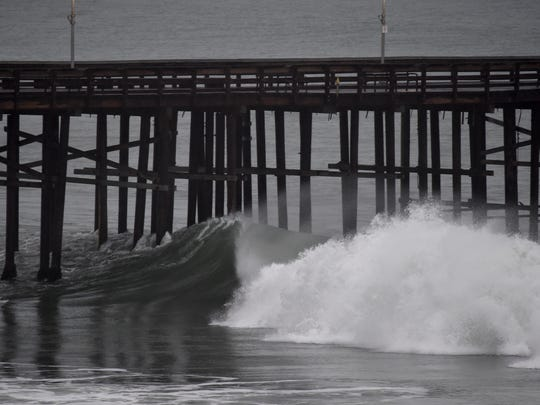 Waves crash near the Ventura Pier as a storm brought rain to Ventura County early Friday.