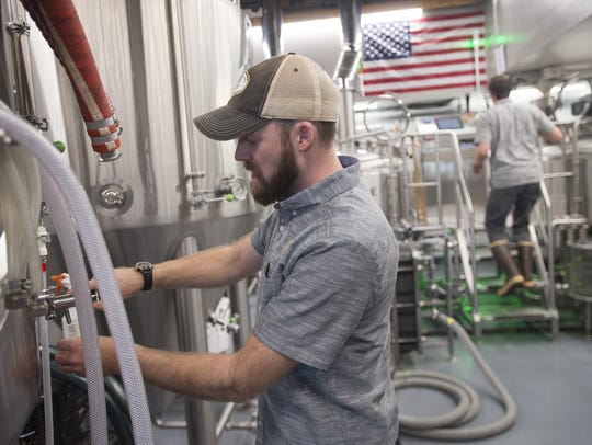 Charlie Hoxmeier takes a sample of fermenting beer