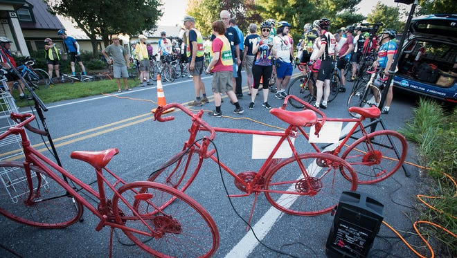 Three red bikes, representing three riders that were injured Saturday, July 22, were dedicated Monday evening, at the intersection of Lawn and Colebrook, South Londonderry. The cyclists were injured when they were deliberately struck by a vehicle. Police continue to search for the driver of the SUV.
