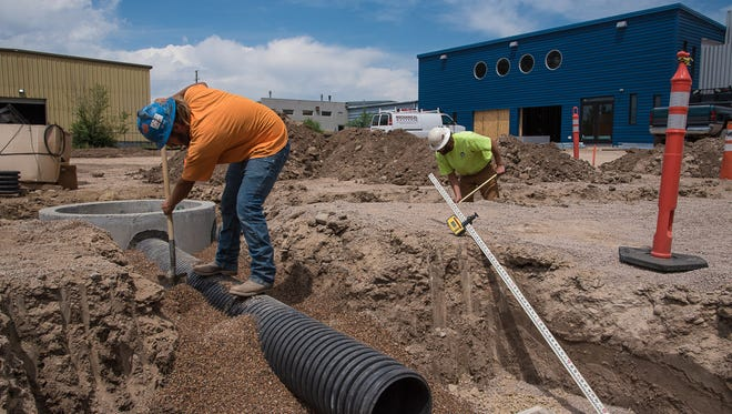 Construction workers dig outside the back entrance of the under-construction  Lyric Cinema Cafe, located at 1209 N. College Ave., on Wednesday, June 28, 2017.    The 10,000 square foot building is tentatively scheduled to open in September.
