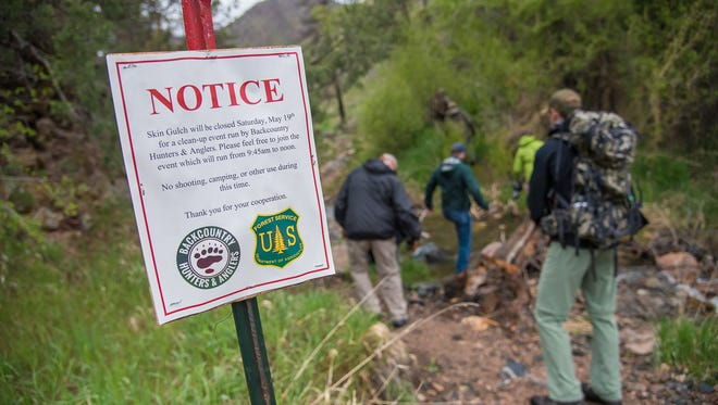 Members of the Backcountry Hunters and Anglers trek down the Skin Gulch trailhead in Poudre Canyon on Saturday, May 19, 2018, as they  begin a litter clean-up in a recreational shooting area.  The group organized the volunteer event to coincide with Colorado Public Lands Day.