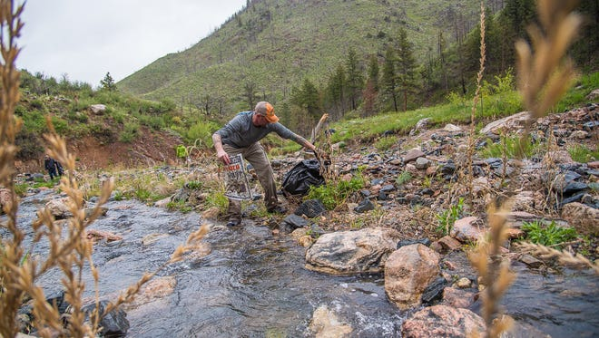 Jason Lukach gathers trash at Skin Gulch in Poudre Canyon on Saturday, May 19, 2018, during a  litter clean-up in a recreational shooting area.  Members of the Backcountry Hunters and Anglers  organized the volunteer event to coincide with Colorado Public Lands Day.