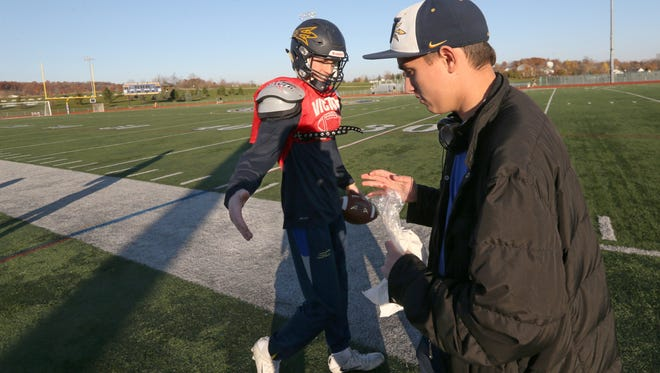 Team manager Jake Rosser, right, gets a high-five from senior quarterback Clay Bleier as he takes the field at the start of practice at Victor High School Thursday, Nov. 17, 2016 in Victor.