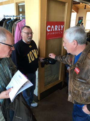 John Nieland holds a fundraising hat after an event Friday for Republican presidential candidate Carly Fiorina in Marion, Iowa.