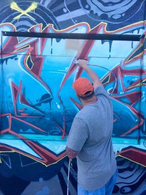 Jedediah Poulsen starts painting over the Chez Quan's mural Sunday to meet a city code enforcement deadline.