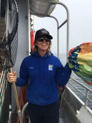 Crew member Taylor Robinson poses with the balloon she fished out of the ocean on a recent Island Packers cruise from Ventura to the Channel Islands. Sea animals can die from ingesting the shiny material.