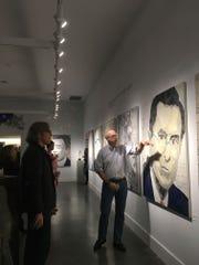 Artist Geoffrey Stein, right, points to his portrait of Stephen Colbert.
