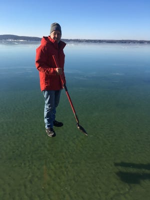 Andre Poineau stands on the very clear ice of a frozen Lake Charlevoix on Jan. 15, 2017.