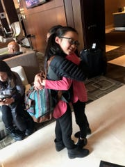 Gracie Rainsberry smiles as she hugs her identical twin, Audrey Doering goodbye after three days in New York City.