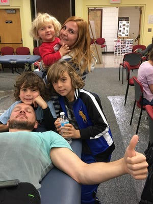 Township resident Mikhail Grushin gives the thumbs up while donating blood at a recent Red Cross blood  drive in the Millburn Free Public Library and setting a good example for his wife Larisa and children Adrian, Serge and Mitchell.