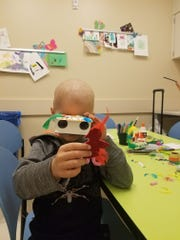 """Five-year-old Nate Campbell of Collingswood peers through the """"bird-noculars"""" he made at Children's Hospital of Philadelphia Friday. The kindergartner was diagnosed with leukemia after his teacher and school nurse recognized his coloring was off."""