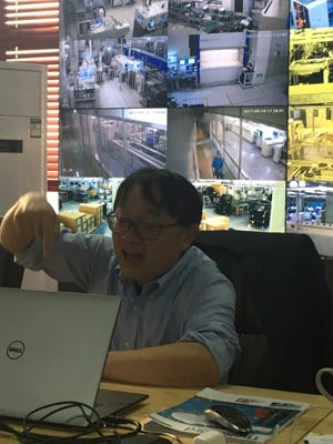 Gerald Wong, CEO and president of Cambridge Industries Group, talks in front of video screens of his factory.