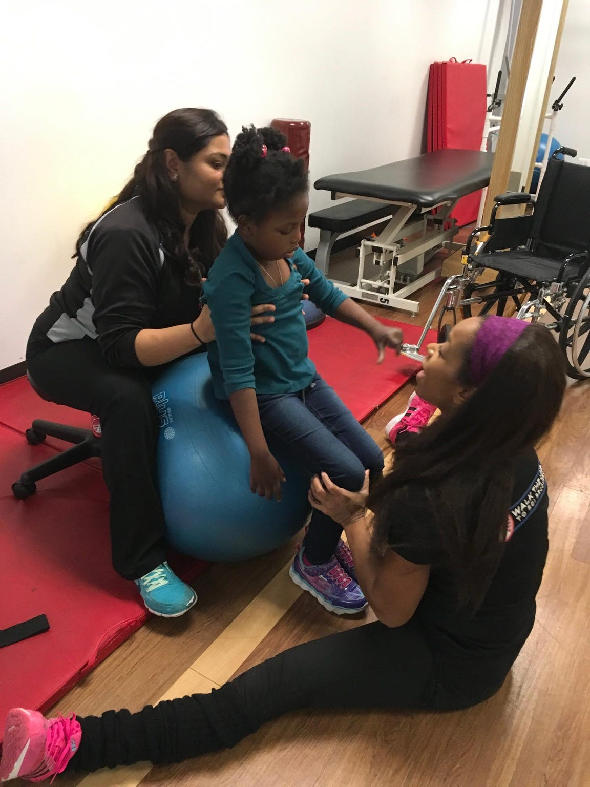 Chika gets help from physical therapists Shruti Joshi, left, and Mia Grimes in January 2017 at Walk The Line To SCI Recovery center in Southfield.