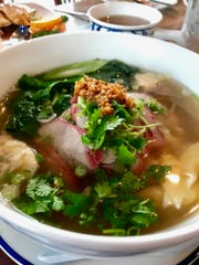 The roasted pork wonton noodle Soup egg noodles has sliced roasted pork, wontons, Chinese kale and cabbage in homemade Thai noodle broth, topped with scallion, cilantro, fried garlic and white pepper powder.