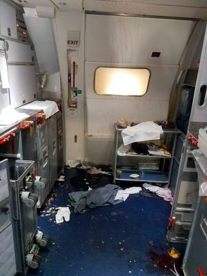 This Friday, July 7, 2017 photo taken the FBI and released via the U.S. Attorney's Office in Seattle shows the aftermath of a cabin on Delta Flight 129 from Seattle to Beijing, after authorities say flight attendants struggled with Joseph Daniel Hudek IV, a passenger who lunged for an exit door.
