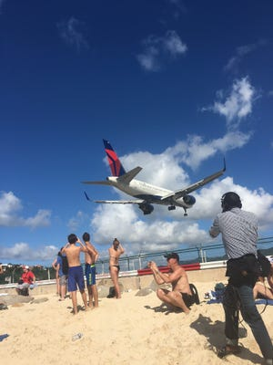 This file hoto from April 2016 shows a plane arriving just above the heads of beachgoers at Princess Juliana International Airport in St. Maarten.