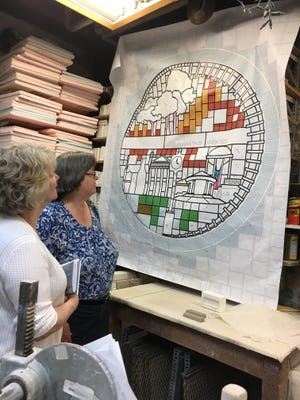 Library staffers Susan Stoney and Carol Souchock take a closer look at the mural layout.