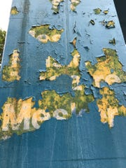The original Mesker Amphitheatre sign peaks through chipped paint in August, 2017.