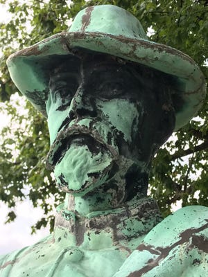 The face of a statue honoring dead Confederate POWs is seen standing in Oak Hill Cemetery in Evansville on Tuesday.