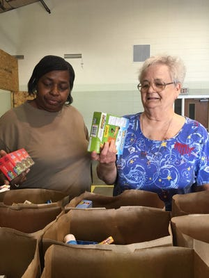 In this file photo, Deborah Turner, left, and Aimee Brown fill grocery sacks full of food at what once was Floral Heights Community Food Pantry. Floral Heights Community Food Pantry is now officially called North Texas Pantry. The board of directors hopes the new name reflects its large demographics.