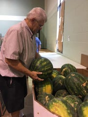 """Jack Helmcamp, a volunteer at Floral Heights Community Food Pantry, loads watermelons into a bin for """"produce day."""" The food pantry is open from 9:30-11 a.m. Monday, Tuesday and Thursday at 2214 10th Street. Several food pantries have closed in the area, and last month Floral Heights Community Food Pantry served 900 families, which equaled 2,820 individuals."""