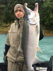KSP Detective Matt Wise shows his catch during an Alaskan retreat for wounded first responders, soldiers.