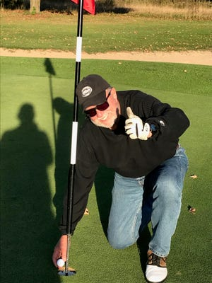 Jim Rossol poses with his golf ball after hitting a hole-in-one on Maxwelton Braes's hole 17