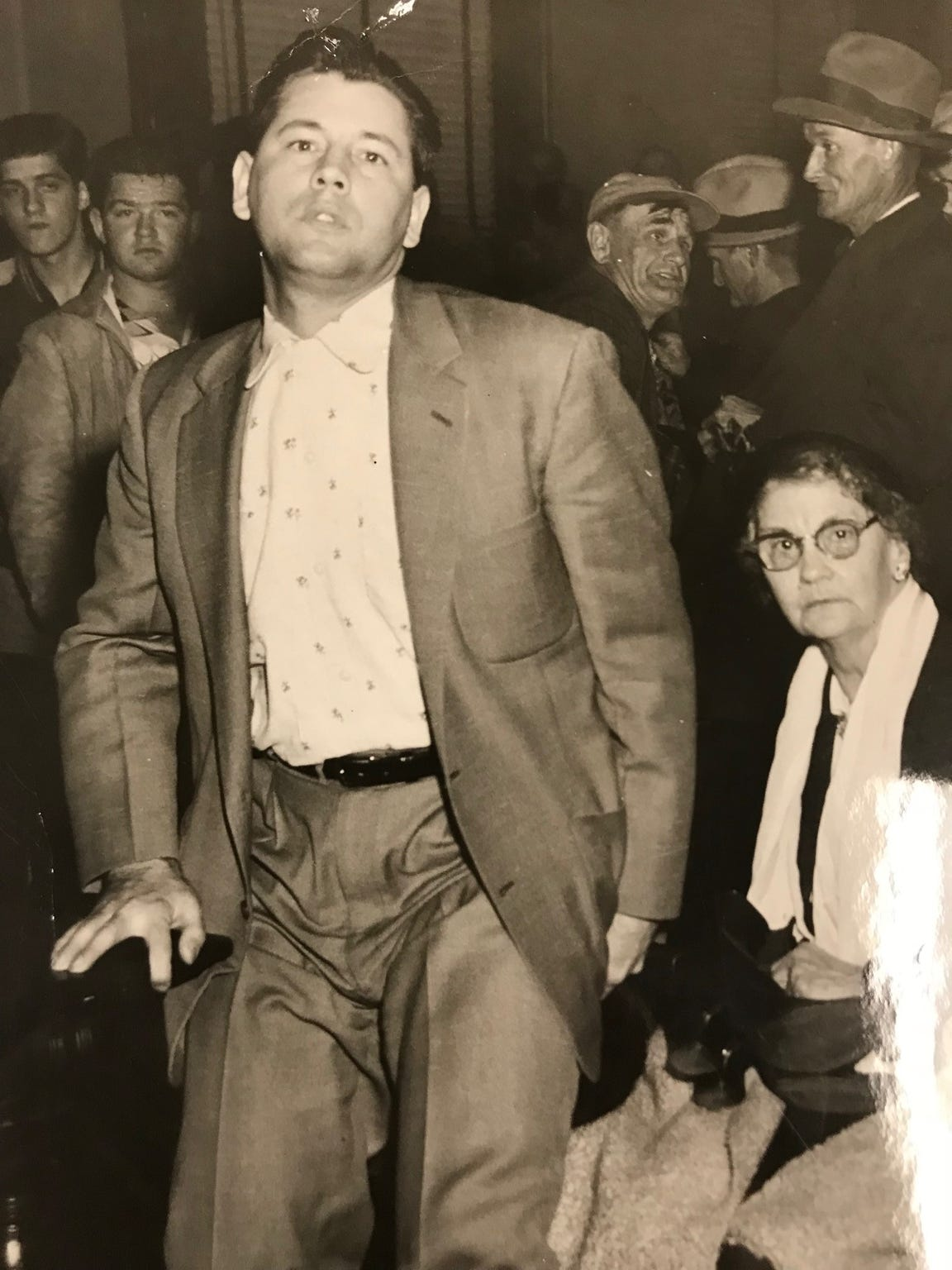 Leslie Irvin stands in the courtroom near his mother during his trial for the murder of Wesley Kerr in December 1955.