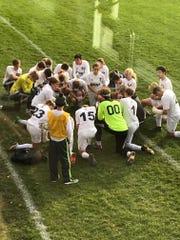 Marshfield Columbus Catholic coed-soccer players huddle