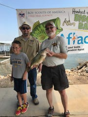 Cub Scout Pack 81 cub master Matt Wunsch Jr. and his son Matt meet with Bill Cox, who was the Big Bass winner at the Texas Trails Council's second annual Hooked on Scouting Bass Tournament at Hubbard Creek Lake.