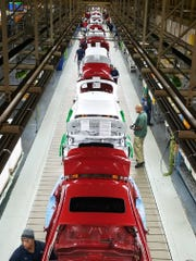 A row of red and white cars roll off the assembly line