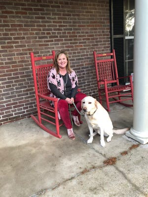 CASA executive director Marianne Schroer sits with CASA dog Rocklin, who provides emotional support to children in court.