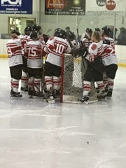 Pacelli co-op hockey players gather around goalie Bryce