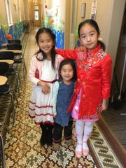 Elena and Ellen Wu, at the festival with their mom Dan Wang (not pictured), and Bella Wen, daughter of faculty member Maria Wang, make a colorful trio.