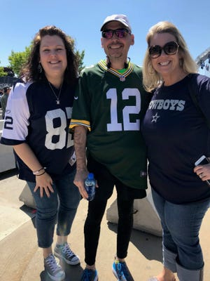 Luxemburg native and diehard Packers fan Bruce Hermans, assistant principal at Coppell Middle School West near Dallas, will run his first Cellcom Green Bay Marathon on May 20. Whether he wears a Packers jersey or a Cowboys jersey for the final mile will depend on which team's fans donate the most to a GoFundMe campaign to benefit the school's choir director, who has oral cancer. He's pictured here with teachers Sunny Richardson, left, and Laura Francis from the school on the day he ran 20 miles to AT&T Stadium to help spread the word.