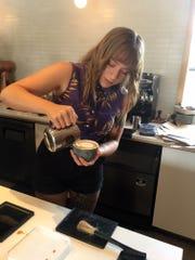 Sarah Ivester hand-sculpts a design on top of a latte.