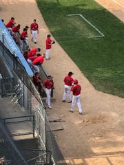 SPASH players slump over the dugout railing and watch