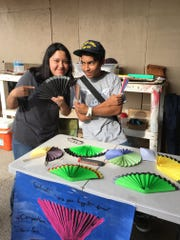"Persephone Saavedra and Jacob Arras show off the handcrafted fans they created for their business, ""FanCraft,"" with partner Brandon Frick. The students participated in Camp Innoventure at William D. Slider Middle School and successfully sold their products at the local flea market."