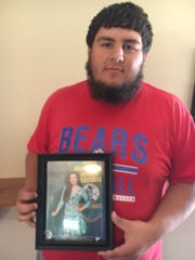 Jake Tibbetts holds a photograph of his sister, Mollie Tibbetts, from a high school speech competition. He is proud of her fearless nature and hopes she will be found.