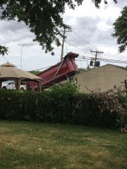 The raised bed of a dump truck became tangled in power lines in Greece on July 24, 2018, a day after a similar incident occurred in Henrietta, causing widespread damage.