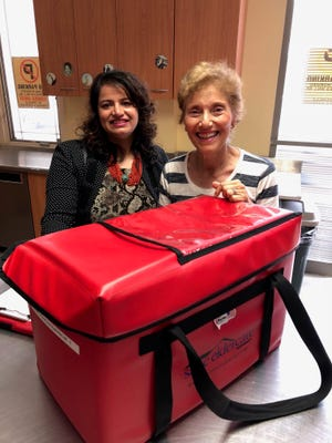 "The Rotary Club of Summit — New Providence visited SAGE Eldercare as part of Rotary's new program ""Rotary for Community."" Fifteen volunteers came to deliver Meals on Wheels and work with clients in the Spend-A-Day Adult Day Health Care program. Pictured is Rotary Club President Swati Goohra of New Providence with Meals on Wheels volunteer Linda Delma of Summit."